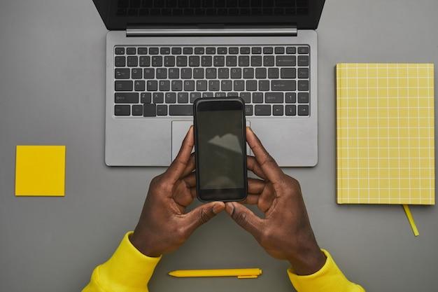 机、トップダウンビュー、コピースペースで作業中にラップトップ上に空白の画面でスマートフォンを保持しているアフリカ系アメリカ人男性の手のグラフィックの灰色と黄色の背景