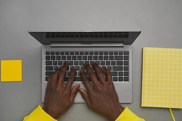 机、トップダウンビュー、コピースペースで作業中にラップトップのキーボードで入力するアフリカ系アメリカ人男性の手のグラフィックの灰色と黄色の背景