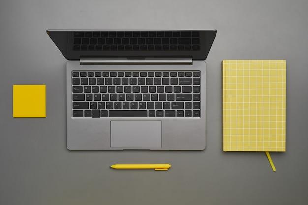 デスクにビジネスアクセサリー、フラットレイトップダウンビュー、コピースペースとラップトップのグラフィックグレーと黄色の背景