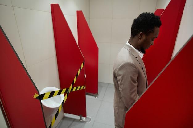 社会的距離と安全対策のためにトイレをテープで止めて公衆トイレを使用しているアフリカ系アメリカ人のビジネスマンのグラフィック画像、コピースペース