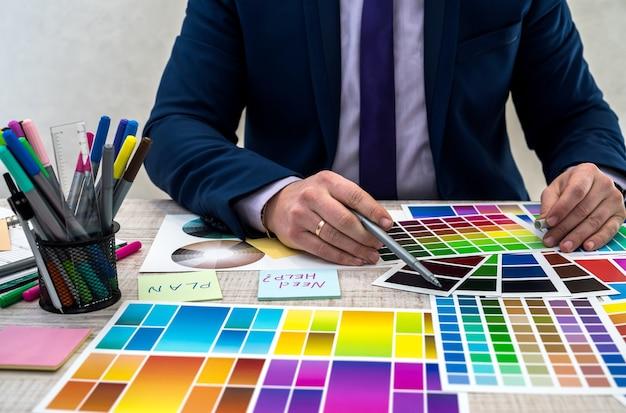 Графический или интерьерный молодой дизайнер в костюме, выбирая цвет из образца образца или справочника палитры каталога на рабочем месте. графический дизайнер с образцами цветовой палитры краски за столом, крупным планом