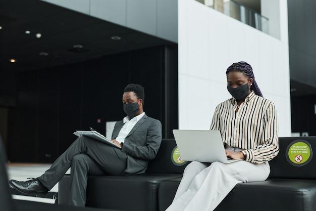社会的な距離で空港の待機ラウンジで働いている間マスクを身に着けている2人のアフリカ系アメリカ人のビジネスマンのグラフィックの肖像画