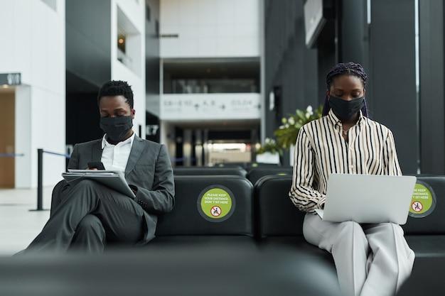 社会的な距離で空港の待機ラウンジで働いている間マスクを身に着けている2人のビジネスマンのグラフィックの肖像画