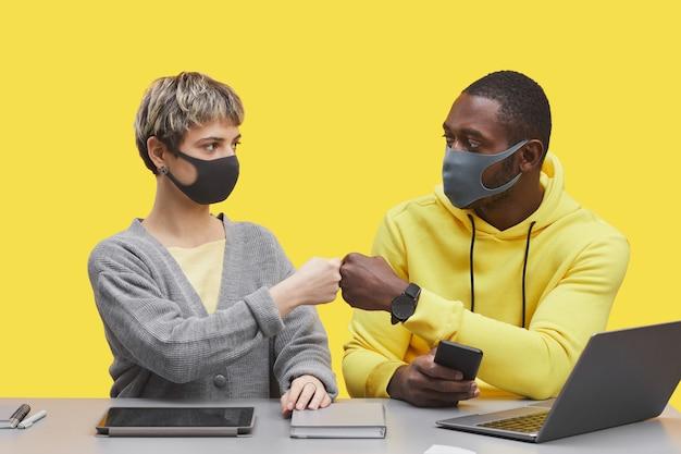 ポップな黄色の背景、コピースペースに対してデスクで一緒に作業しながらマスクとぶつかった拳を身に着けている2人の現代のビジネスマンのグラフィックの肖像画