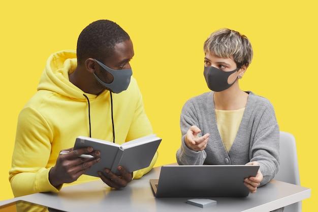ポップな黄色の背景に対してデスクで一緒に作業しながらマスクとぶつかった拳を身に着けている2人の若いビジネスマンのグラフィックの肖像画