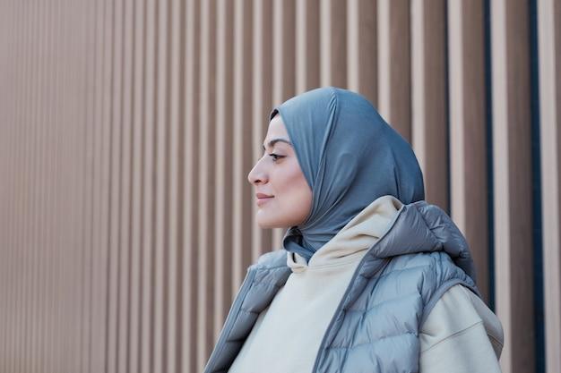 屋外でスカーフを身に着けている現代中東の女性のグラフィックの側面図の肖像画、強いプロファイル、コピースペースに焦点を当てる