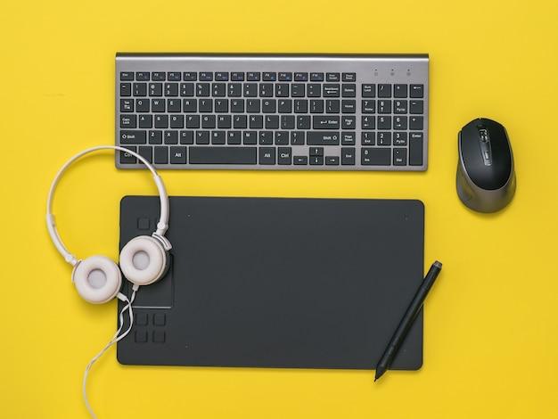 노란색 배경에 그래픽 태블릿, 키보드, 마우스 및 헤드폰. 디자이너의 도구.
