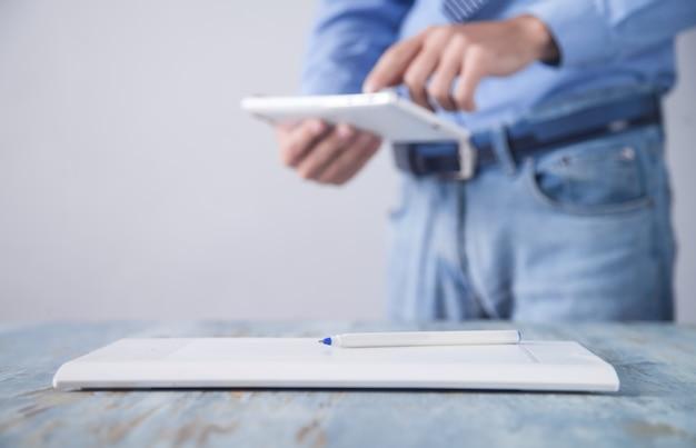 机の上のグラフィックタブレット。白いデジタルタブレットを使用している男。