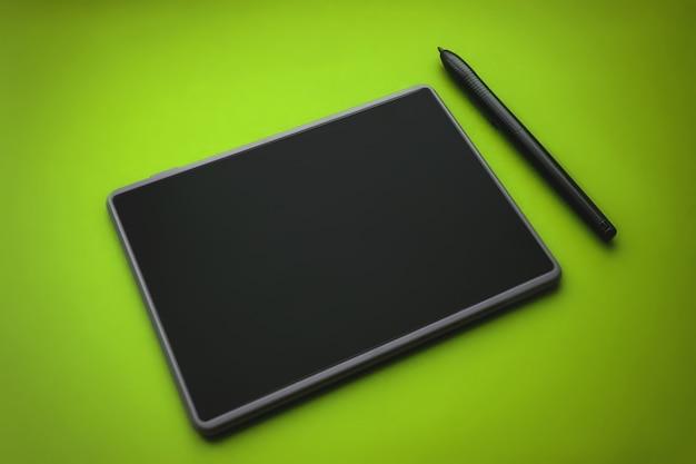 장치 표면에 있는 그래픽 태블릿 펜, 클로즈업 사진. 녹색 배경에 삽화가와 디자이너를 위한 펜이 있는 그래픽 태블릿.