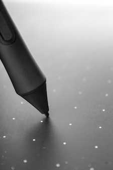Graphic tablet pen on the surface of the device, close-up photo.