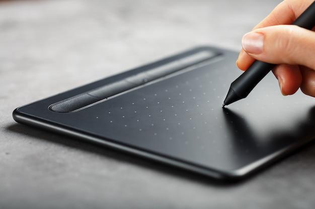 디자이너의 손에 펜으로 그래픽 태블릿 클로즈업. 창의성과 작업을위한 가제트