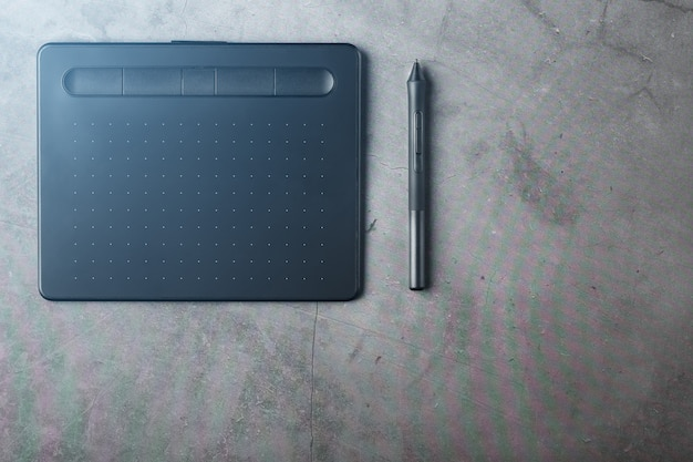 暗いテクスチャ背景、上面にスタイラスが付いたグラフィックタブレット。デザイナー、アーティスト、写真家として働くためのガジェット