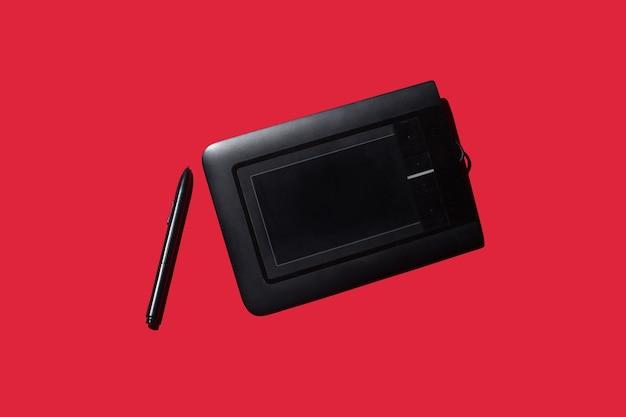 Графический планшет с ручкой на красном фоне