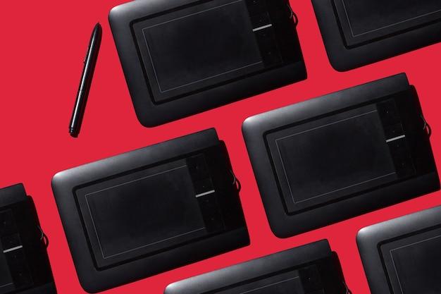 赤い背景のデザインのためのペンとグラフィックタブレット創造性の概念