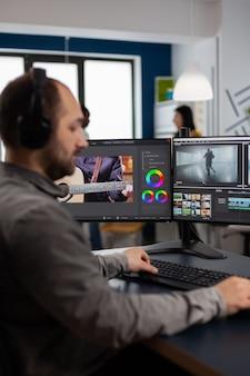 창의적인 작업 공간에 앉아 비디오 및 오디오 푸티지를 편집하는 두 개의 디스플레이가 있는 pc에서 작업하는 그래픽 비디오 제작