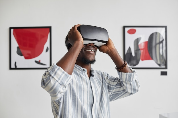 Graphic waist up portrait of smiling african-american man wearing vr gear while enjoying immersive experience at modern art gallery exhibition,