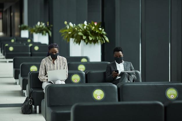 社会的な距離と空港の待機ラウンジでラップトップで作業しながらマスクを身に着けているアフリカ系アメリカ人のビジネスマンのグラフィック広角の肖像画