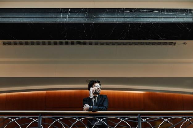 고급 호텔의 발코니에 서서 스마트폰으로 말하는 성공적인 중동 사업가의 그래픽 와이드 앵글 초상화, 복사 공간