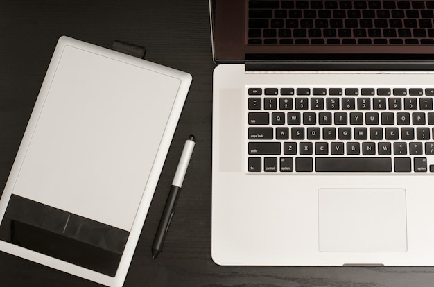 Graphics tablet with a pencil, some laptop on black wooden table, close-up