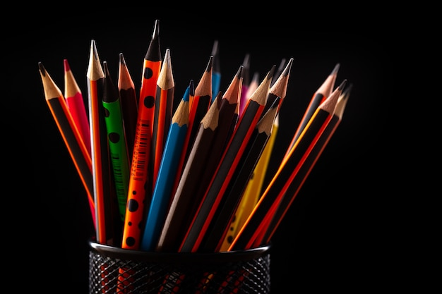 Graphite colorful pencils for drawing and writing inside black little basket on black desk