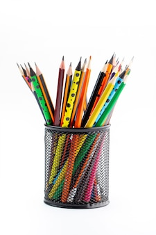 Graphite drawing pencils bright lined inside black basket on white desk