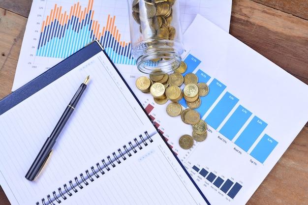 グラフ、チャート、ノート、ペン、コイン。ビジネスコンセプト