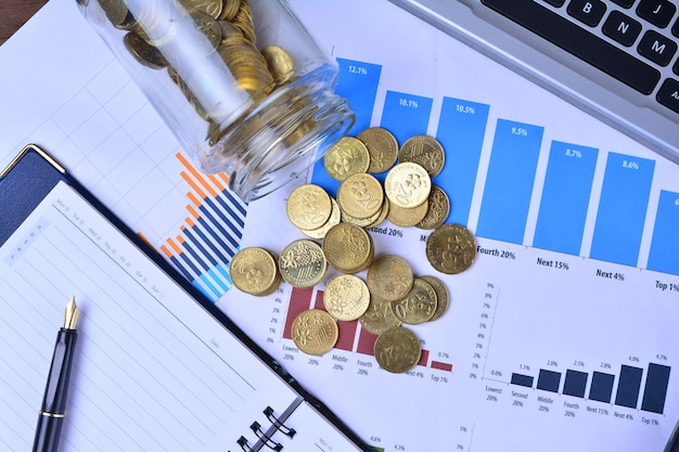 Graphs, charts, notebook, pen and coins. business concept
