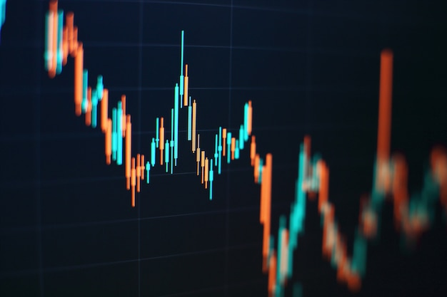 Торговля на графиках, в том числе восходящего и нисходящего тренда. гистограмма свечей экрана монитора фондовой биржи бизнес-значения выросла концепции.