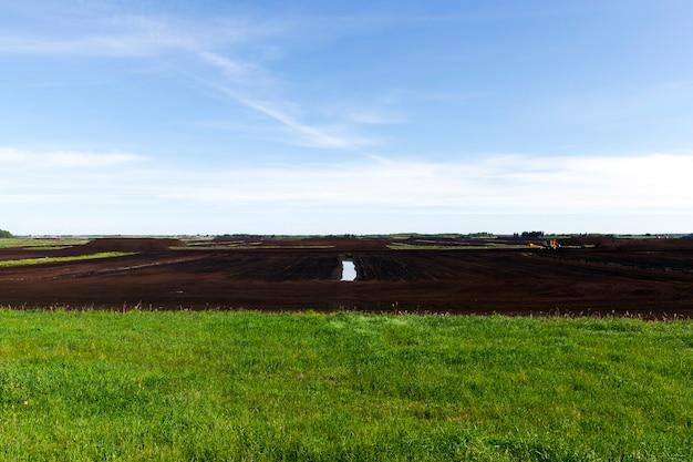 産業での抽出の場所での草と黒泥炭、青い空の夏の風景