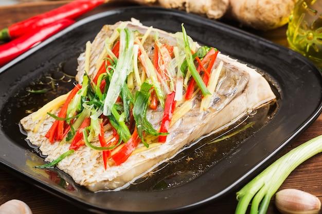 草carのフィレ蒸し魚蒸し草car魚の皮生gとネギ入り Premium写真
