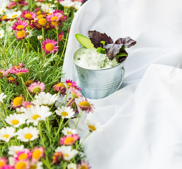 Grass with flowers, picnic tablecloth and a cup of yogurt with herbs.