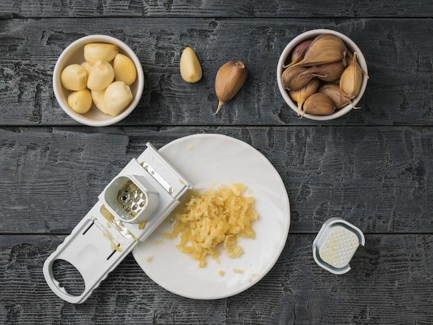 木製のテーブルの上にボウルにすりおろし、すりおろしたにんにく。キッチンに人気のスパイス。