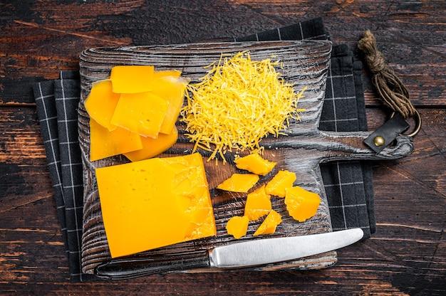 木製のまな板の上にすりおろしてさいの目に切ったチェダーチーズ。暗い木の背景。上面図。