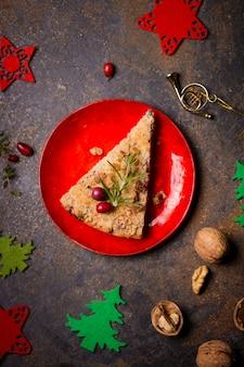 赤いプレートにジャム、クランベリー、ローズマリーを添えたすりおろしたケーキ