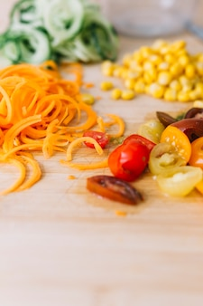 Grated carrot; corn seeds and slices of cherry tomatoes on wooden background