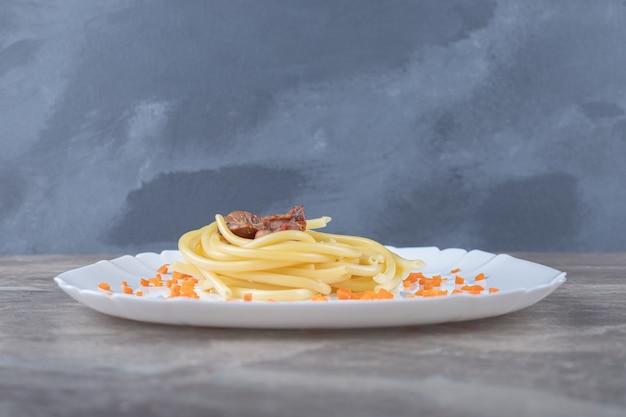 Carota grattugiata e spaghetti con carne alla piastra, sulla superficie di marmo.