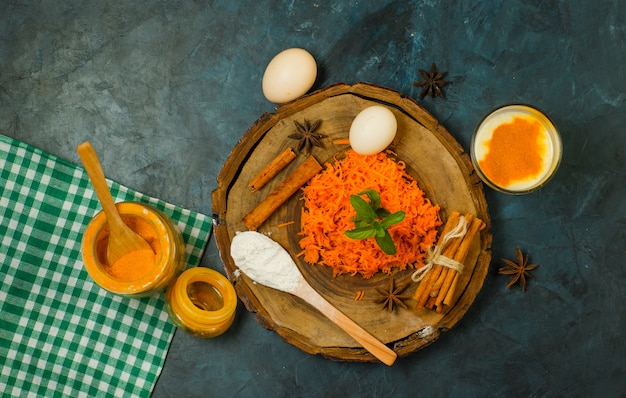 Grated carrot with eggs, flour, spices, milk, picnic cloth on wooden board and stucco background, top view.