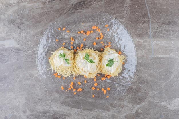 대리석에 유리 접시에 스파게티, 요구르트 및 녹색 야채를 곁들인 강판 당근.