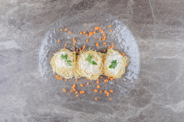 Grated carrots with spaghetti, yogurt and green vegetable on the glass plate , on the marble.