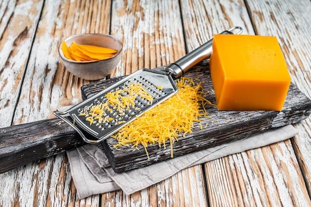 木製のまな板にすりおろしたチェダーチーズ。白い木製の背景。上面図。