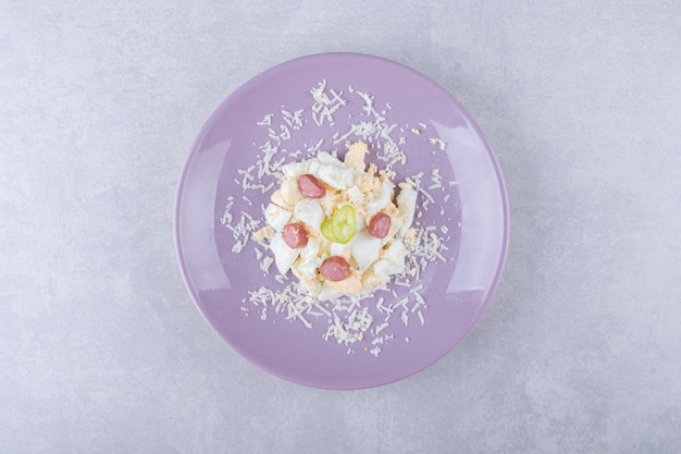 Grated cheese and egg with sausages on purple plate.