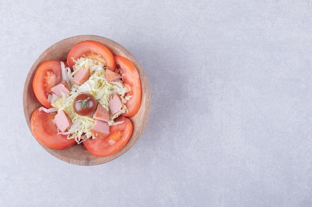 Тертый сыр с сосисками и помидорами в деревянной миске.