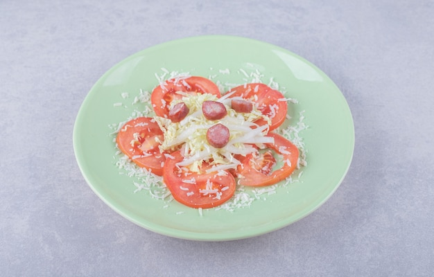 Grated cheese with sausages and tomato on green plate.