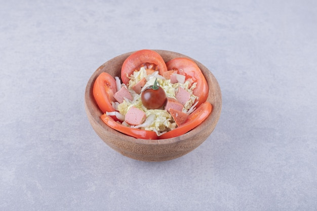 Grated cheese with sausages and tomatoes in wooden bowl.