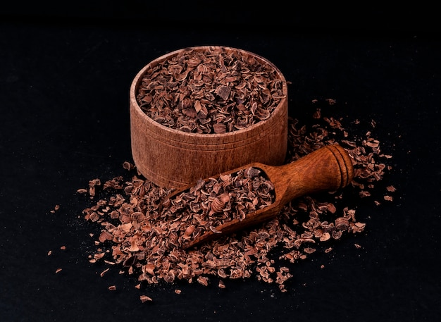 Grated chocolate on black background, closeup