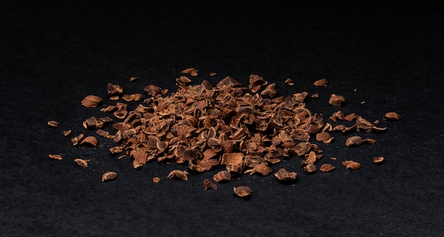 Grated chocolate, heap of ground chocolate isolated on black, closeup