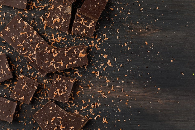 Grated chocolate with choco bars on dark background, flat lay.