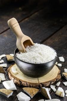 素朴な陶器のボウルにすりおろしたココナッツと計量スプーン。トロピカルフルーツの食材