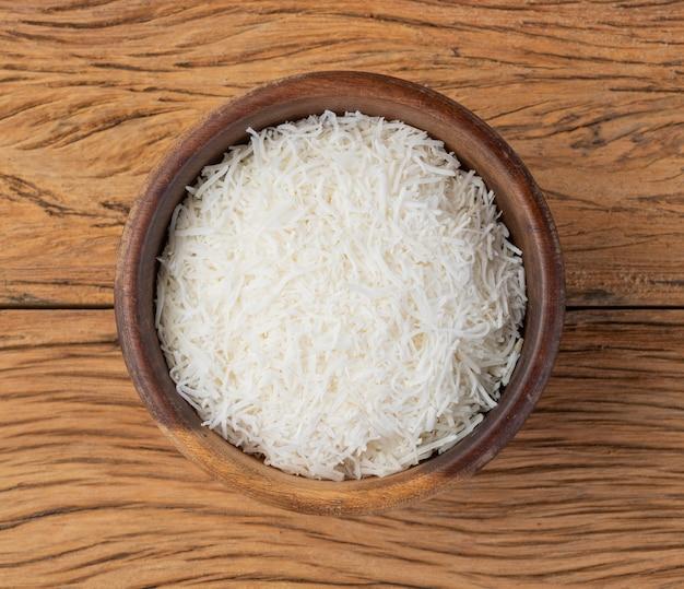木製のテーブルの上のボウルにすりおろしたココナッツフレーク。