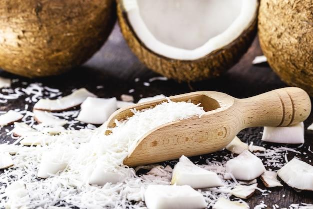 木製の計量スプーンにすりおろしたココナッツ、スライスしたココナッツ部分、キャンディーの材料